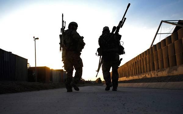 04.大きなライフルを抱えた兵士の後ろ姿を逆行で撮影した写真壁紙画像