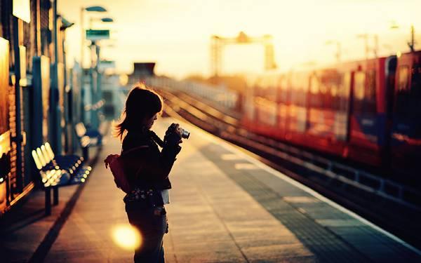 08.夕日のホームに佇むカメラを持った女性の写真壁紙画像