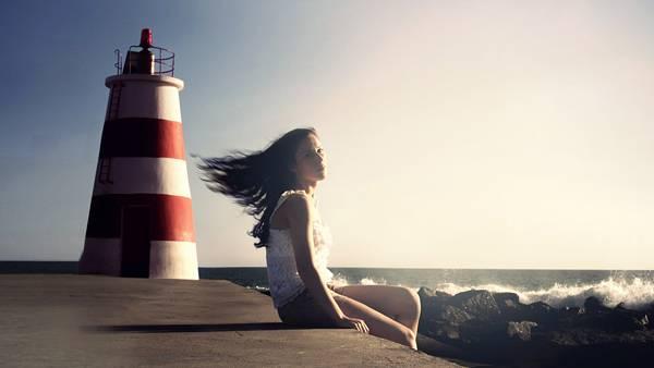 04.灯台と防波堤に座る女性を撮影した綺麗な写真壁紙画像