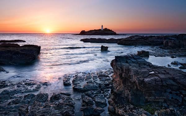 11.夕日の沈む海岸と遠くに見える小さな灯台の写真壁紙画像