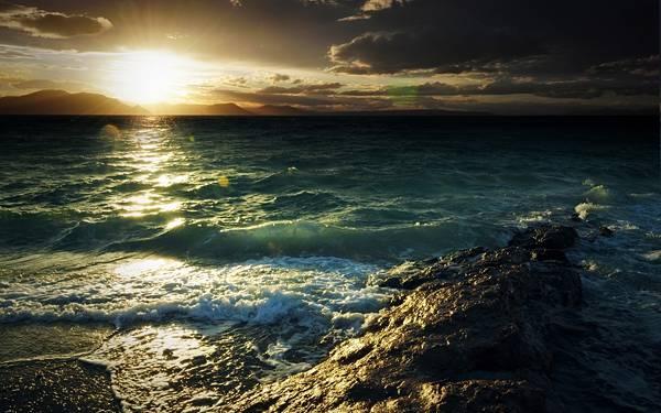02.昇る朝日と荒々しい並の海辺の風景を撮影した写真壁紙画像