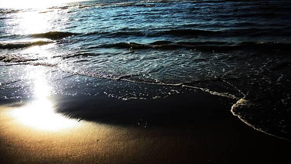 06.太陽を映して光り輝く波打ち際のハイコントラストな写真壁紙画像
