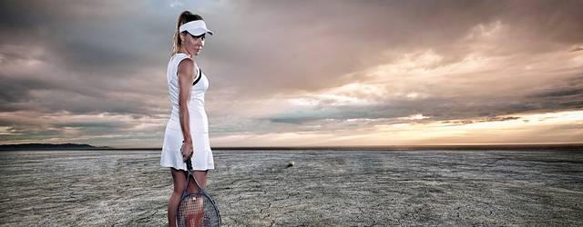 テニスウェアとラケットを持って荒野に佇む女性