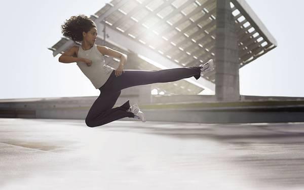03.逆光の中で飛び蹴りをする女性の綺麗な写真壁紙画像