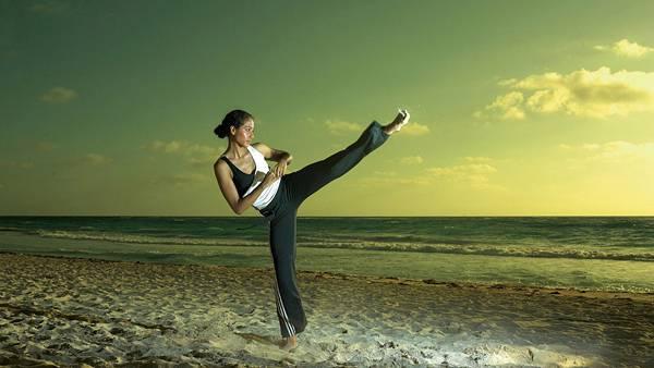 04.波打ち際の砂浜でハイキックをする女性の写真壁紙画像