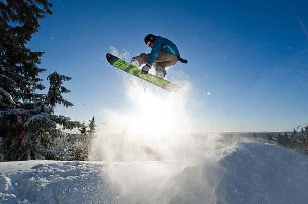 逆光の中でジャンプするスノーボーダーの写真