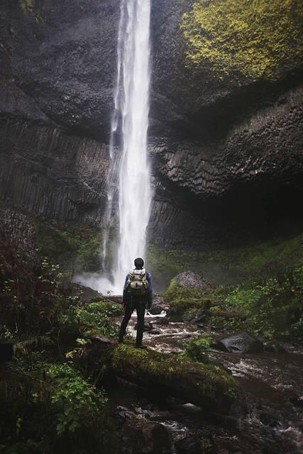 滝を見つめるハイカーの写真