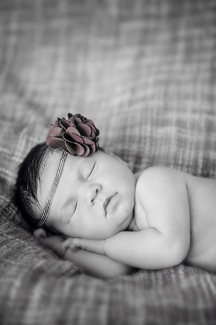 花のコサージュのヘアバンドをした赤ん坊