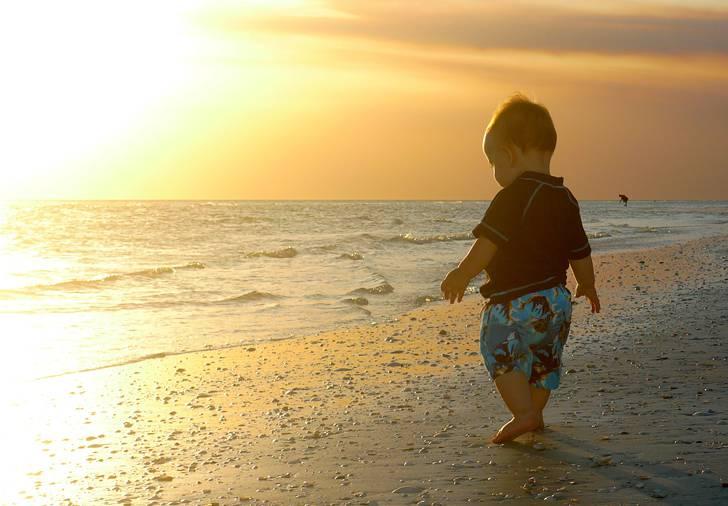夕日の海辺を歩く赤ちゃんの写真