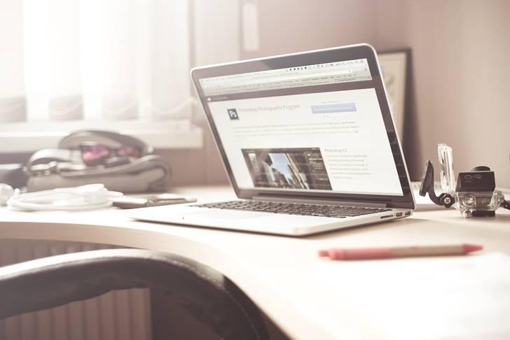 明るい仕事場のMacBookProの写真