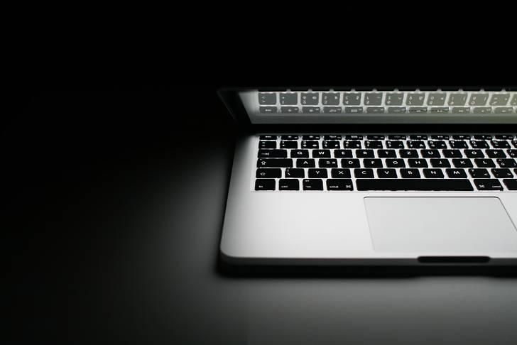 暗闇の中のMacBookProの写真