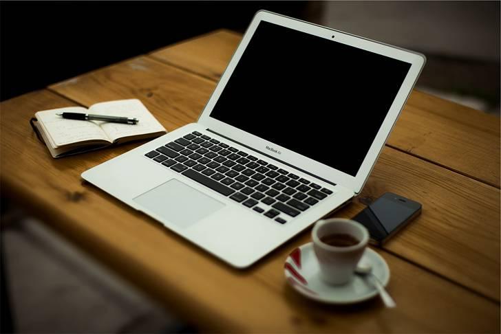コーヒーとメモ帳とMacBookのお洒落な写真