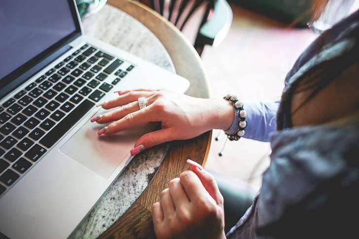 カフェでMacを使う女性のノマド風写真