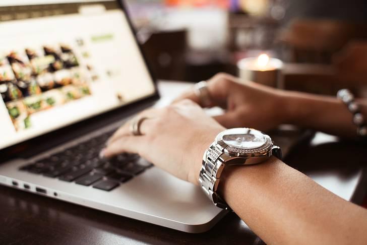 腕時計をしてタイピングする女性の手元