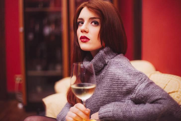 グラスに入った白ワインを持つ女性の写真素材