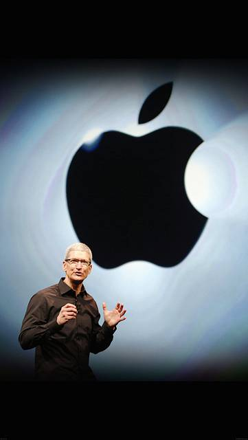 Appleロゴを背景にプレゼンするティム・クック