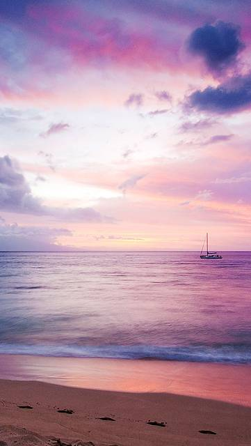 紫色の夕日の海と船の美しい写真