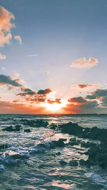 沈む夕日と海岸の岩の写真画像