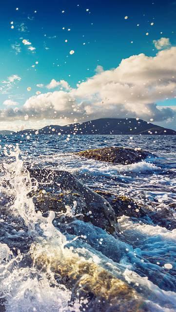 波しぶきと海と島の綺麗な写真