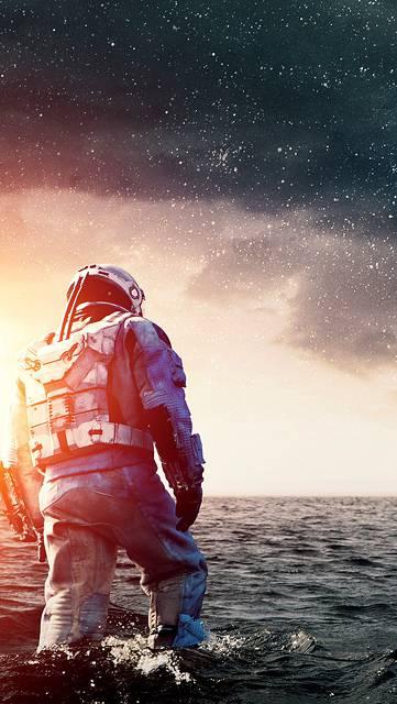 海と宇宙服を着た人物