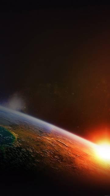 地球の夜明けと輝く太陽