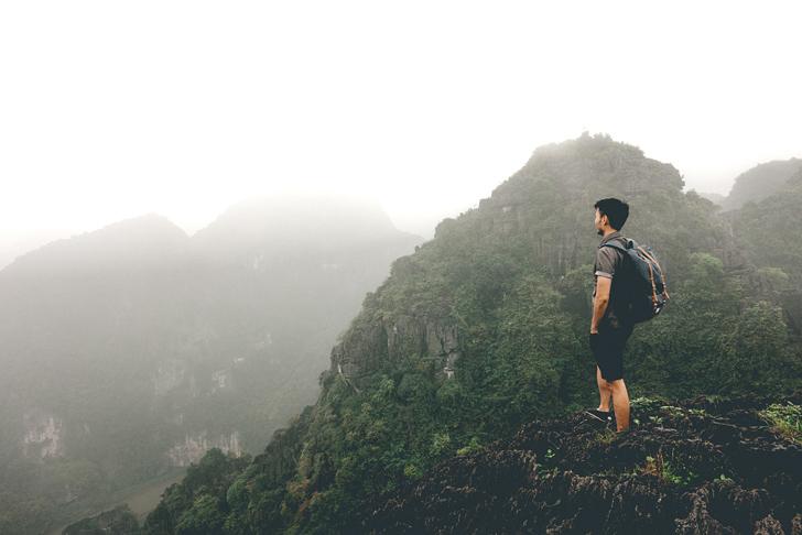 山を見下ろすバックパッカーの男性